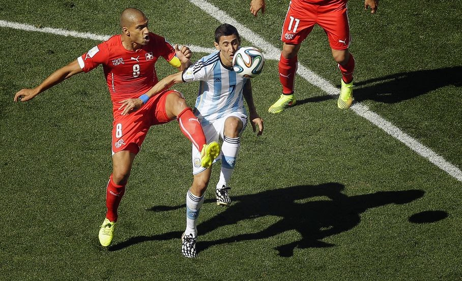 Switzerland's Goekhan Inler, left, and Argentina's Angel di Maria challenge for the ball during the World Cup round of 16 soccer match between Argentina and Switzerland at the Itaquerao Stadium in Sao Paulo, Brazil, Tuesday, July 1, 2014.