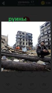 мужчина сидит на бревне на заднем плане руины домов