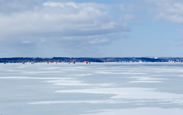 Ice fishing huts on a frozen lake in Orillia, Ontario
