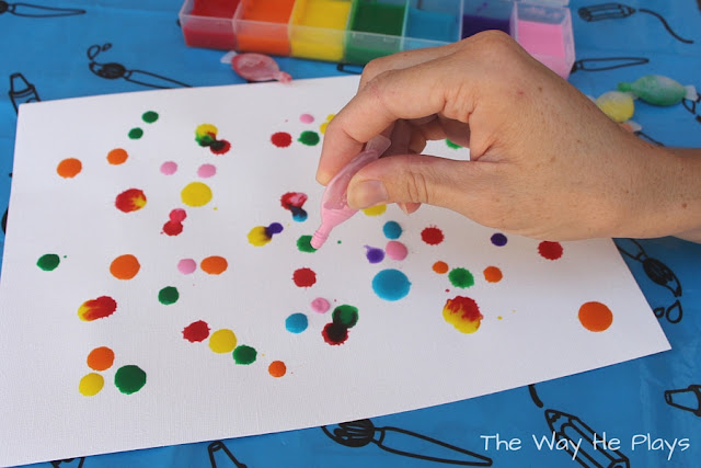 Colourful drops of paint on the paper.
