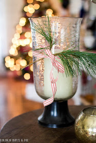 Crate and Barrel seeded glass hurricane with fresh greenery and ribbon