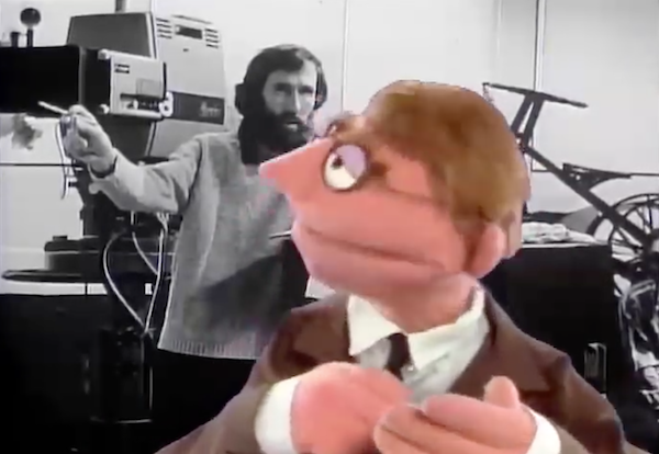 Muppet with glasses, suit, and tie in front of black-&-white photo of Jim Henson on TV production set