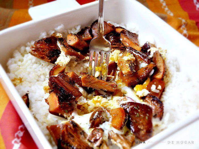 huevos rotos en plato de arroz con níscalos o rebollones