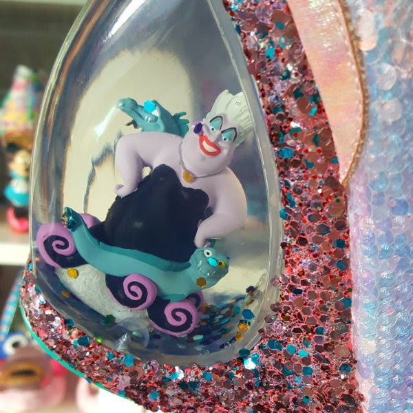 close up of heel of shoe with water and glitter inside and Ursula, Flotsam and Jetsam figures inside
