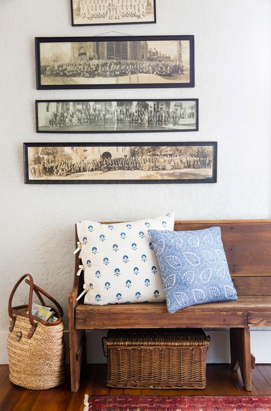 Charming cottage interior with old rustic wood bench, blue pillows, and vintage framed horizontal photographs. Design by Holly Mathis. #cottagestyle #interiordesign #farmhousedecor #vintagestyle #decoratingideas