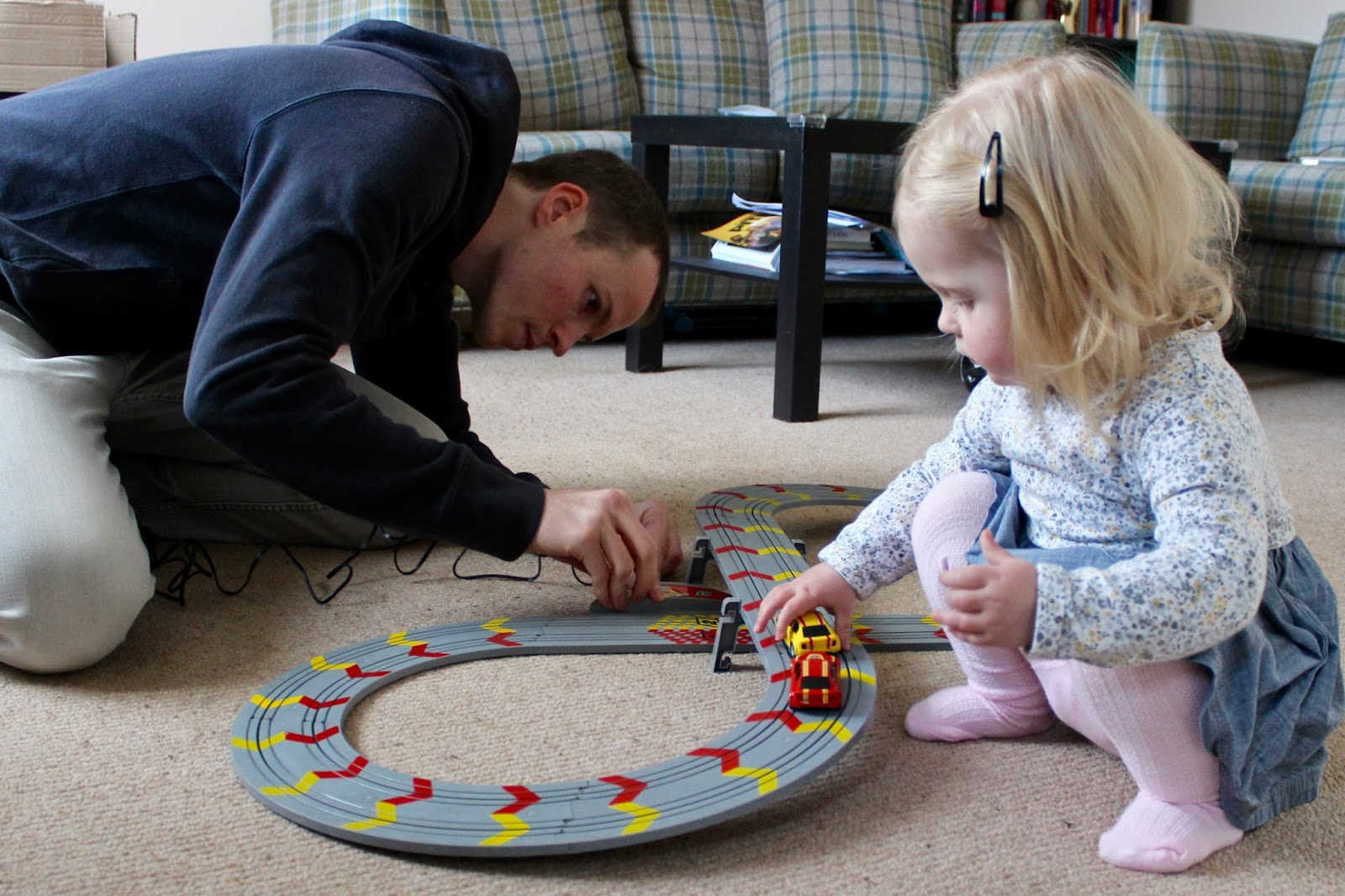 Elise (2 years old) places two cars on the Scalextric track whilst my husband connects the controllers. There is a red car and a yellow car.