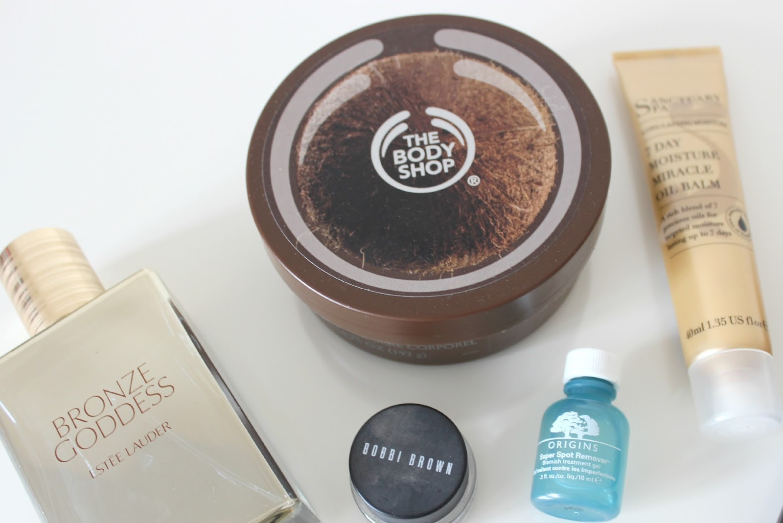 A picture of The Body Shop Coconut Body Butter, Estee Lauder Bronze Goddess and Sanctuary Spa 7 Day Moisture Miracle Oil Balm