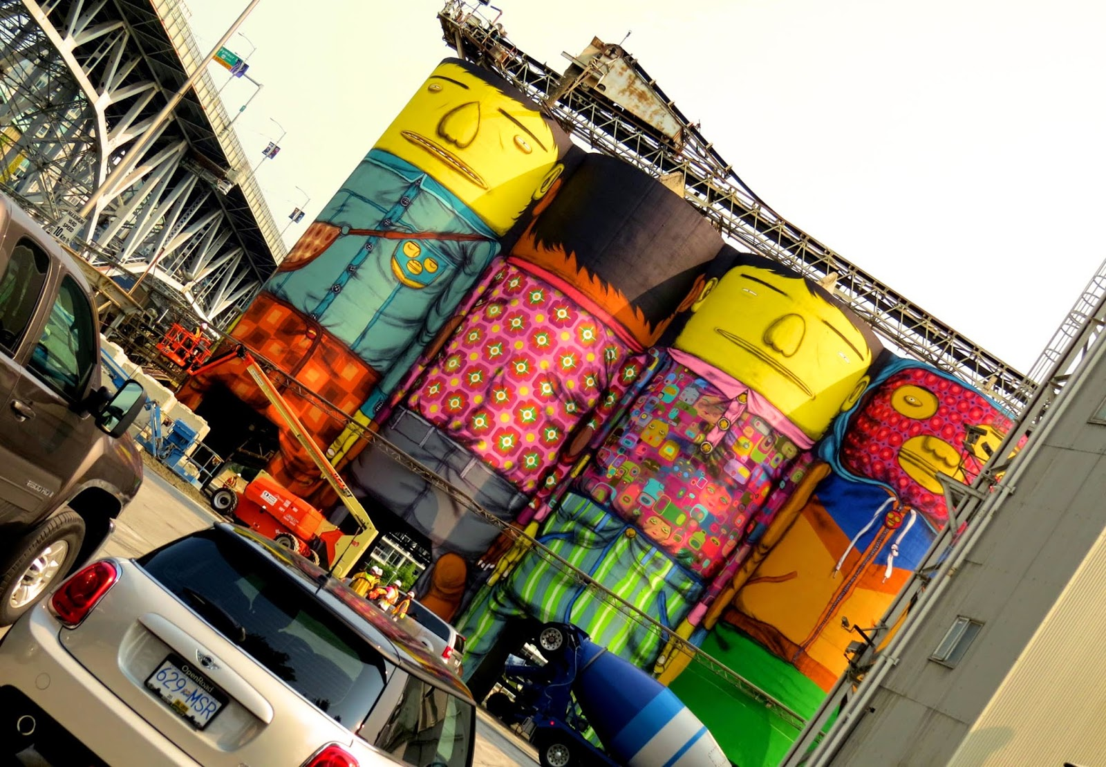 "Os Gemeos are bringing their ""Giants"" project to Canada where they are currently transforming six giant industrial silos with their signature characters for the Vancouver Biennale 2014 on Granville Island in Vancouver."