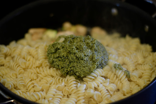 The pesto being added to the pan.