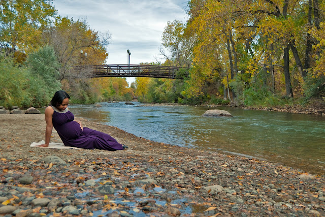 Beautiful photograph of a pregnant woman along a creek in Colorado in autumn