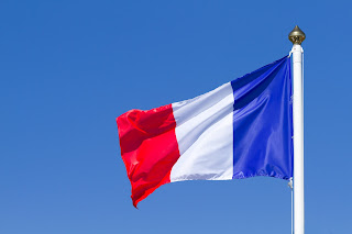 Pic of French flag flying at top of flagpole against clear blue sky