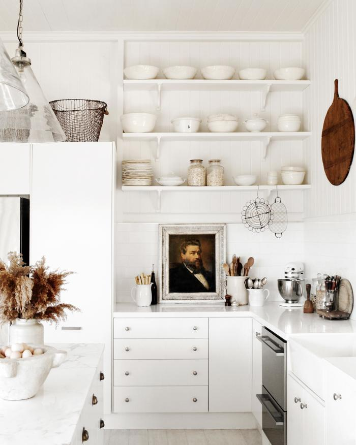 Lovely white stacked kitchen shelves paired with white countertops and cabinets