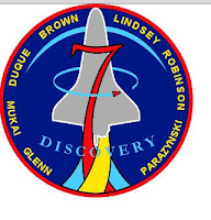Blue back ground with outline of space shuttles and large red numeral 7 and names of crew members around the circumference.