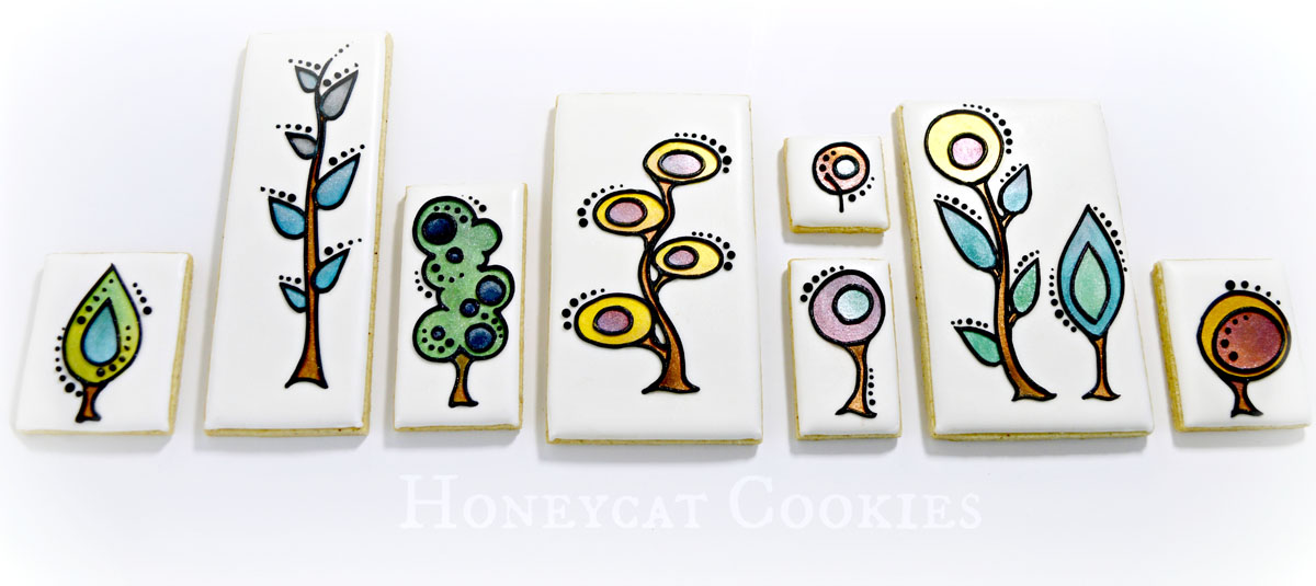 Full set of stylised plant decorated cookies, lined up, ready to eat. By Honeycat Cookies