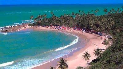 Vista aérea da praia de coqueirinhos ao fundo barracas e pessos na orla