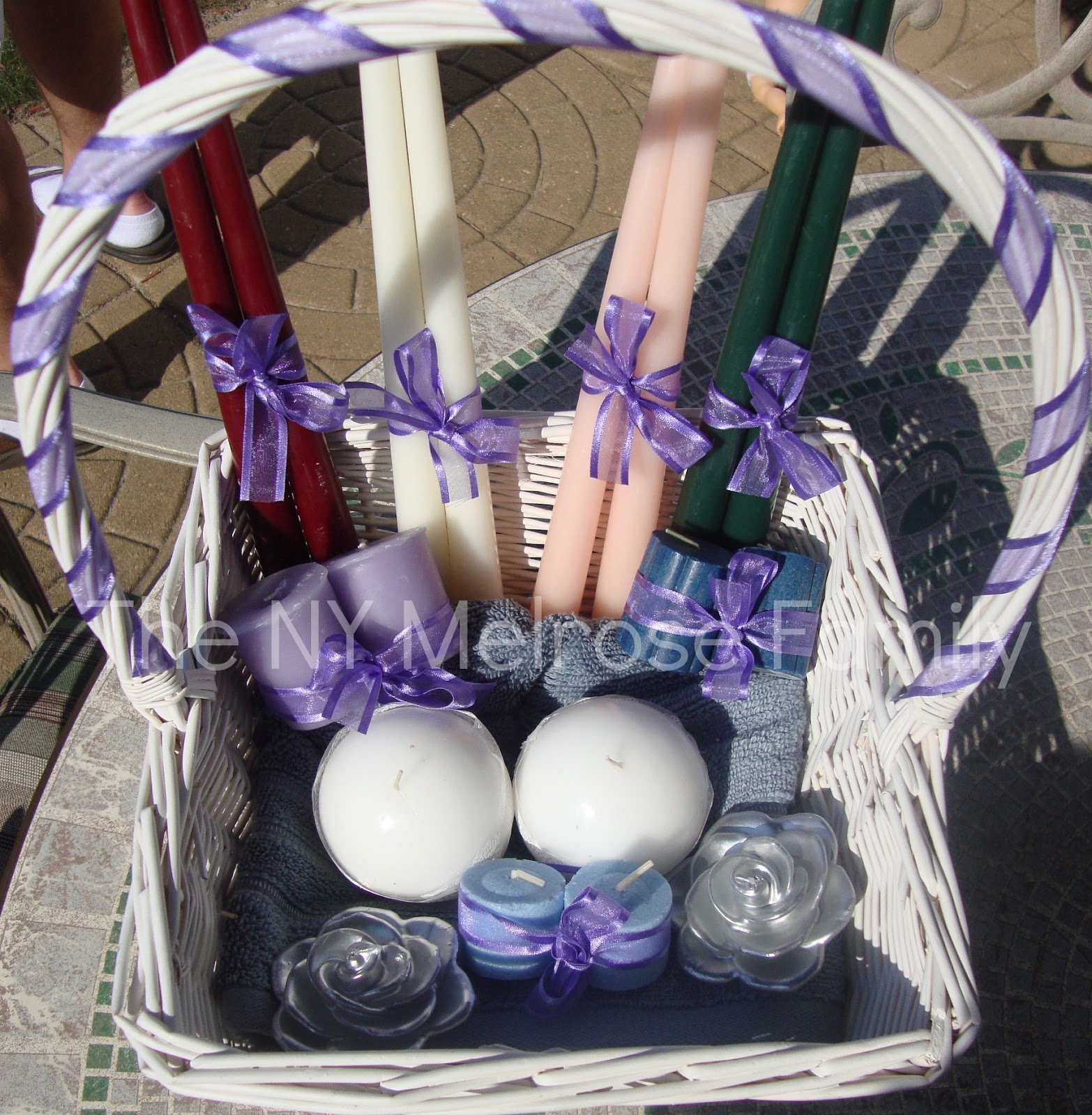 f64c1fbab9c84b I wrapped a purple ribbon around the handle of the basket. I also tied the  pairs of candles with the same purple ribbon.