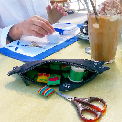 Cafe table with a glass of iced coffee on it. Next to the glass is a cat-shaped pencil case containing miniature cushions, thread and scissors and behind it is a woman working on an appliqué piece.