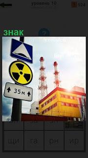 На столбе висит знак опасности радиационной, на заднем плане АЭС