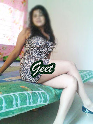 Geet sitting on bed in short dress with open hair