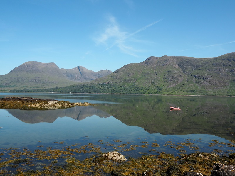 The Torridon hills against a blue sky, reflected in the loch