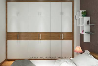 Tủ quần áo và kệ tren tường màu trắng là điểm nhấn nổi bật nhất của căn phòng