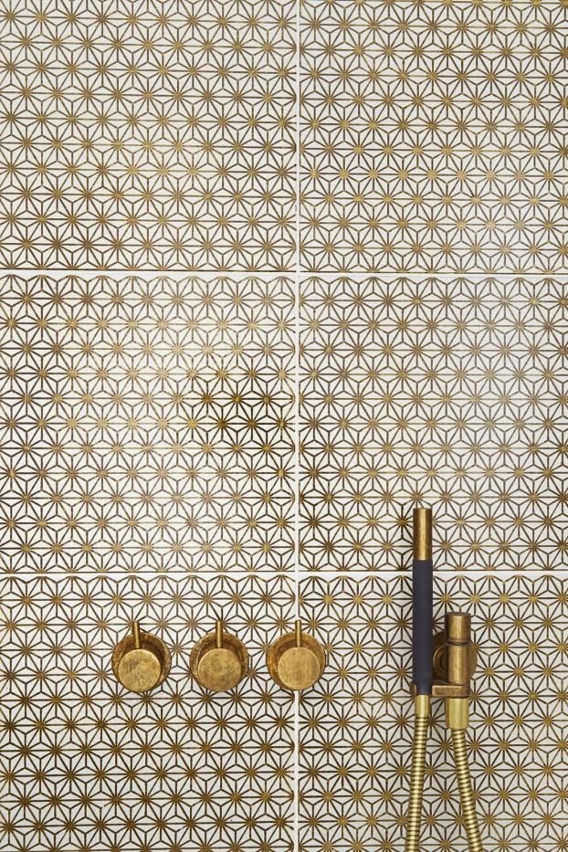 white and gold mosaic with brass faucets