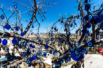 A close-up of bare tree branches with light & dark blue colored circular evil eye amulets. Photo by Hulki Okan Tabak.