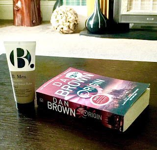 A upside down triangular bottle with a blue and white background with a big black bold b with Post Shave Balm in smaller black font next to a rectangular book saying dan brown in white font on a brown rectangular table  on a bright background