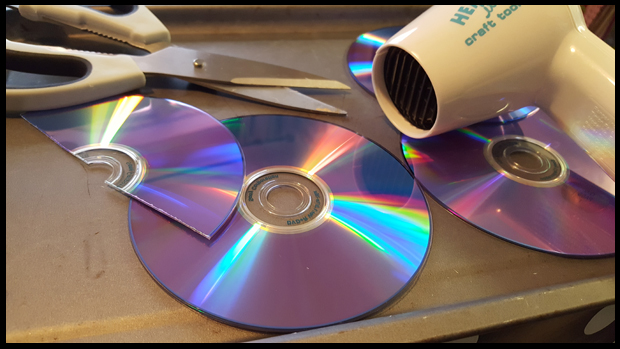 The best way I found to cut DVDs for art projects was to heat them up