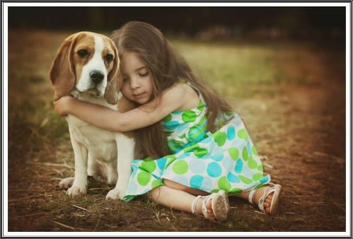 Linda menina sentada no chão, abraça docemente um cachorro que com olhar triste deixa-se abraçar.