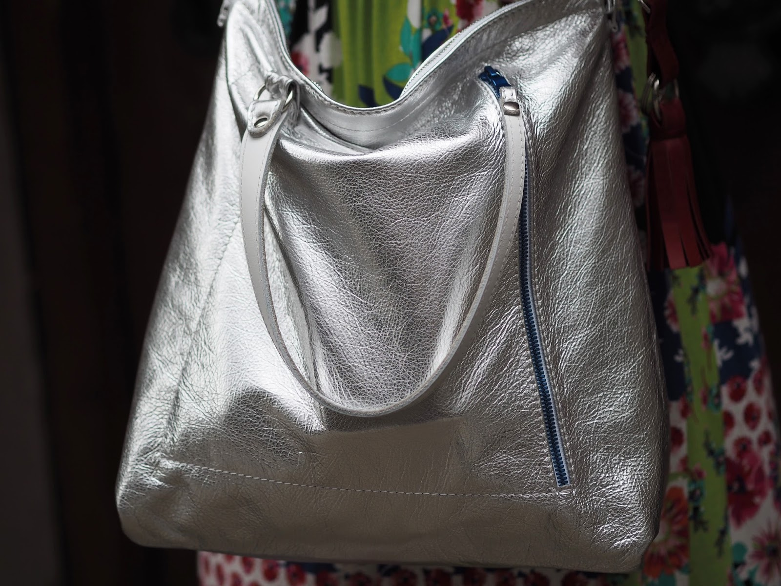 Silver leather tote bag with red zip and blue zip