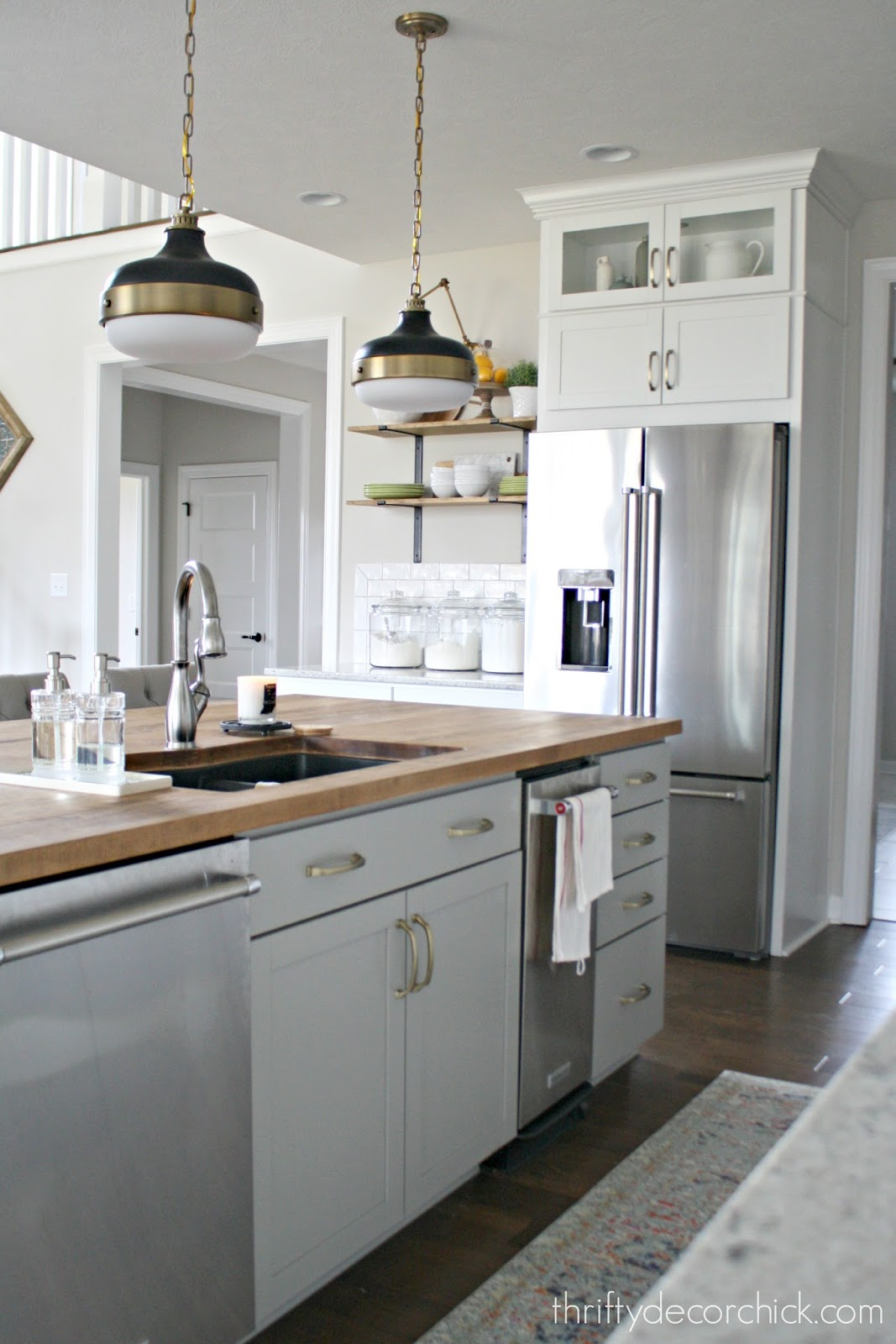 Gray island with wood countertops and sink