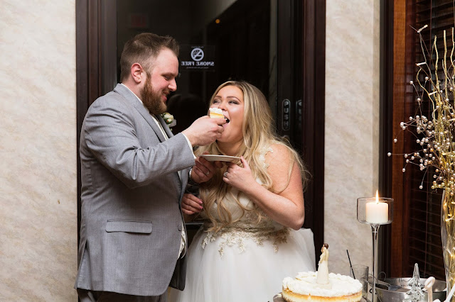 bride and groom feeding each  other cake at italian american cultural center in Clinton Township