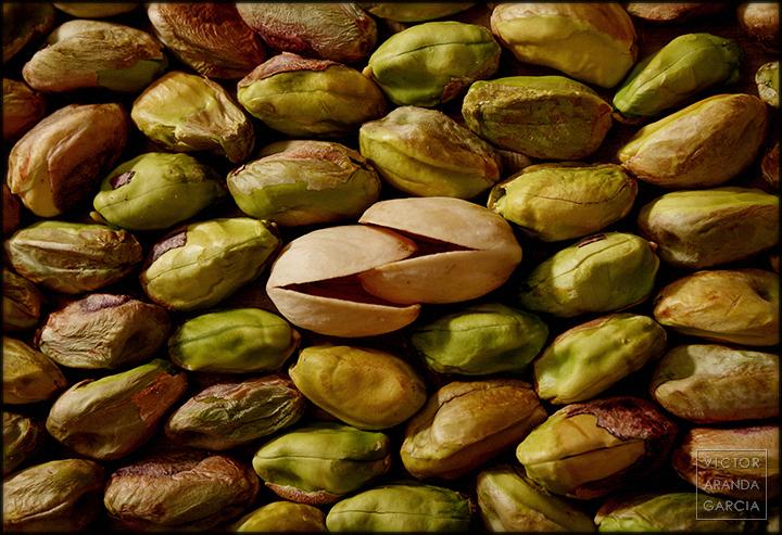 Fotografía de dos cáscaras de pistacho engarzadas como en un beso rodeadas de los frutos coloridos del pistacho