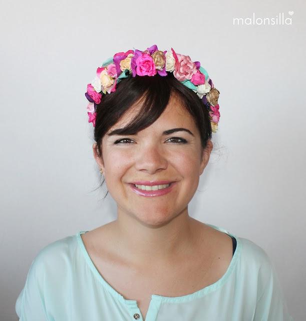 Chica de frente con look de diadema flores en varios colores, predomina el fucsia