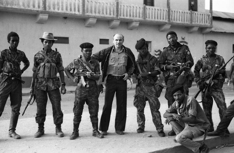 fotografia przedstawiająca żołnierzy MPLA. Kapuściński stoi w centrum, opierając rękę na ramieniu jednego z nich.
