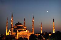 Gün batımında gökyüzünde hilal ay varken Sultanahmet Camisinin bir resmi