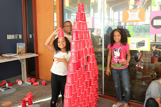 A young boy and two girls stand beside a tower made of red plastic cups. The youngest girl wears a cup on her head as a pretend hat.