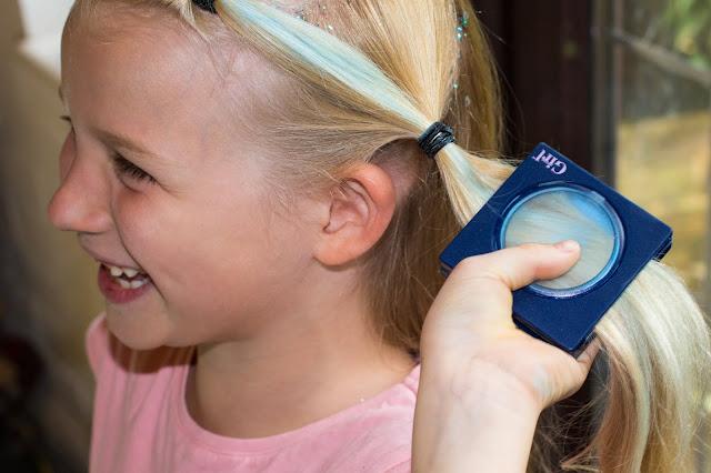 A smiling girl applying blue hair chalk