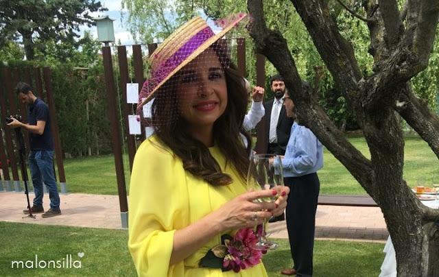 Invitada boda con sombrero canotier de ala ancha y copa baja color cardenal, vestido amarillo.