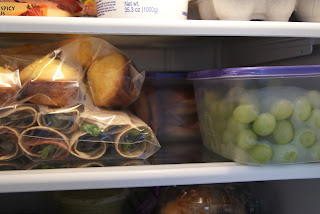 Prepped lunches in plastic bags and plastic containers, in the refrigerator.