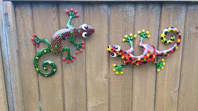 Decorative metal gecko sculptures on the fence.