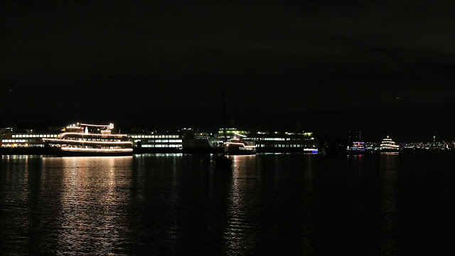 A parade of boats with Christmas lights at night.