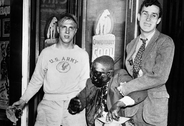Two youths help a man to his feet after he was badly beaten in street fighting which marked race riots in Detroit, Michigan, on June 21, 1943.