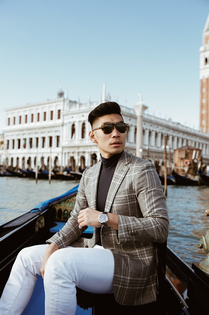 Leo Chan wearing a blazer with jeans in Venice, Italy