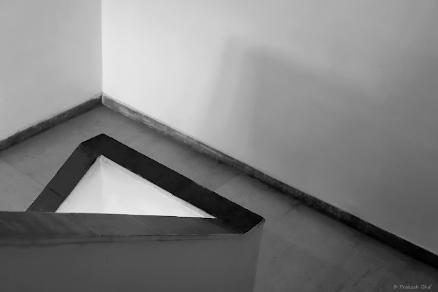 A Black and White Minimal Art Photograph of a Staircase located at Jawahar Kala Kendra and a White Triangle being formed between its Side Rails.