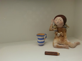 Close-up view of a gallery display of a miniature clay figure, blue and white striped jug and pencil