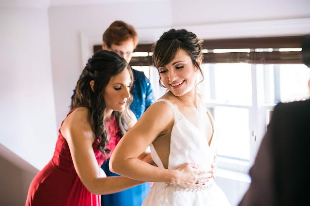 a black haired bride with her hair pulled up is being helped into her wedding dress by her black haired sister in a red dress while her mom in a blue dress stands in the background in front of a window