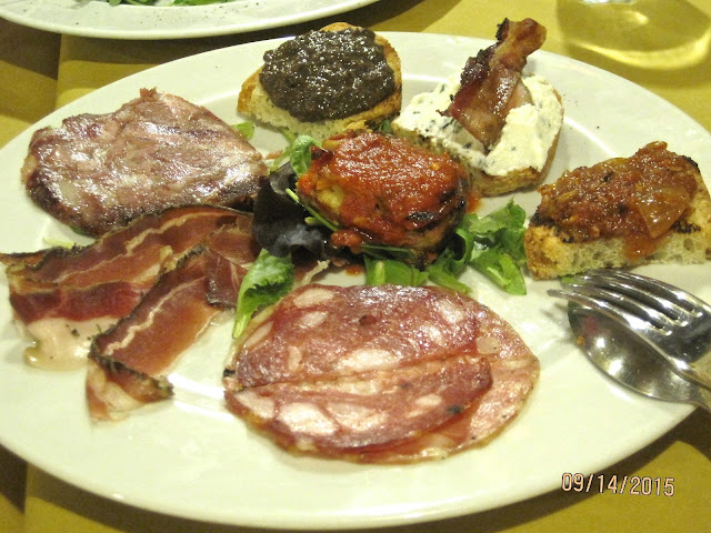 platter of bruschetta with various meat topping