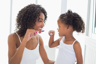 An adult and a child brushing their teeth together
